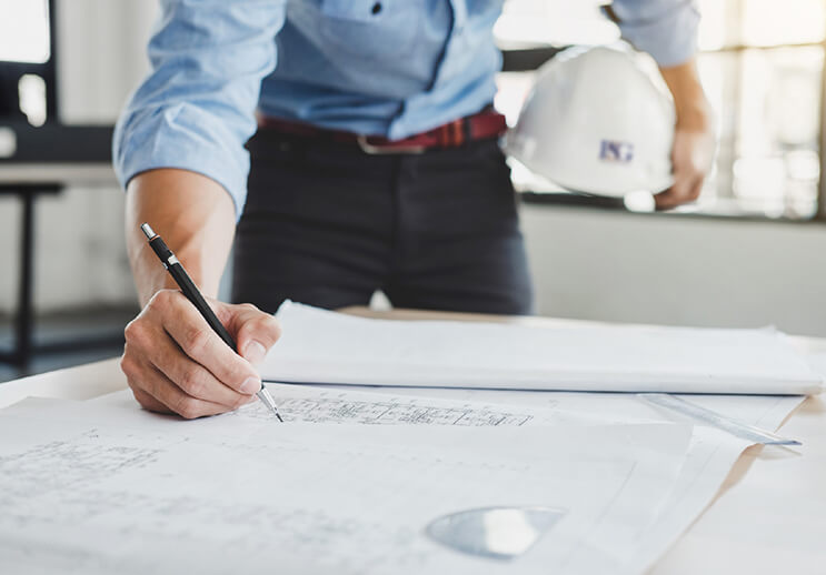 Canva Man Holding HHat Working Blueprints